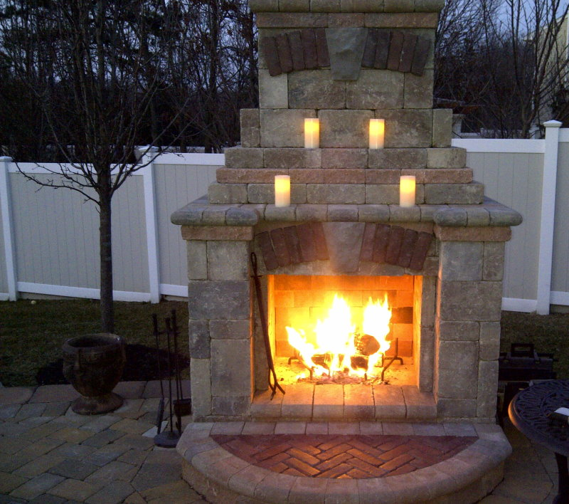 outdoor unilock fireplace with candles on mantle