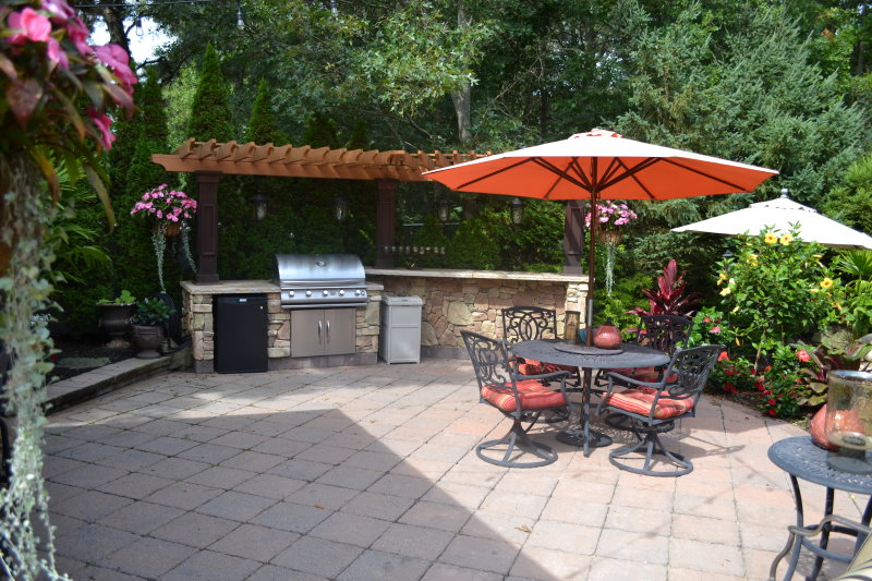 outdoor kitchen island with pergola and lights