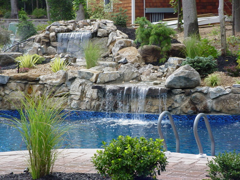 beautiful moss rock water feature into pool