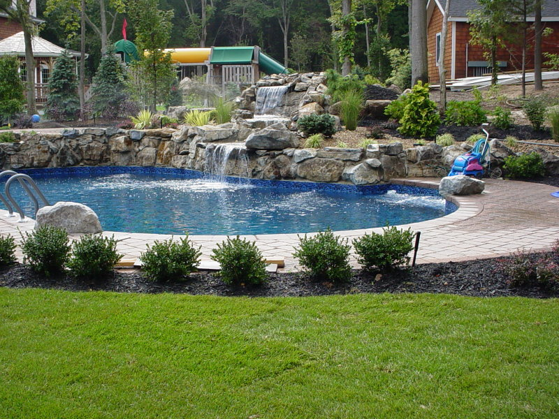 large scale moss rock water feature into pool