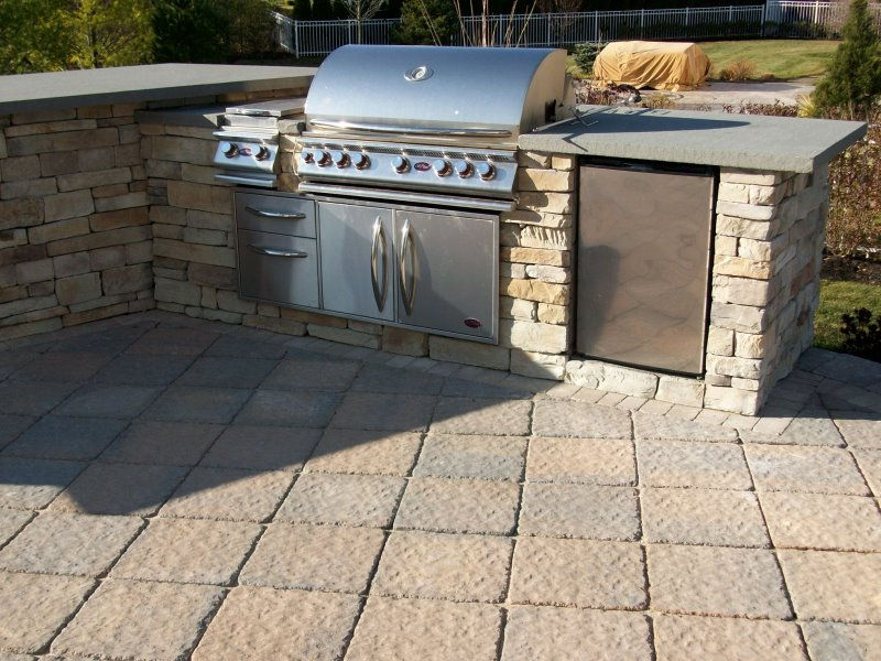 outdoor kitchen island with cultured stone and bluestone counter