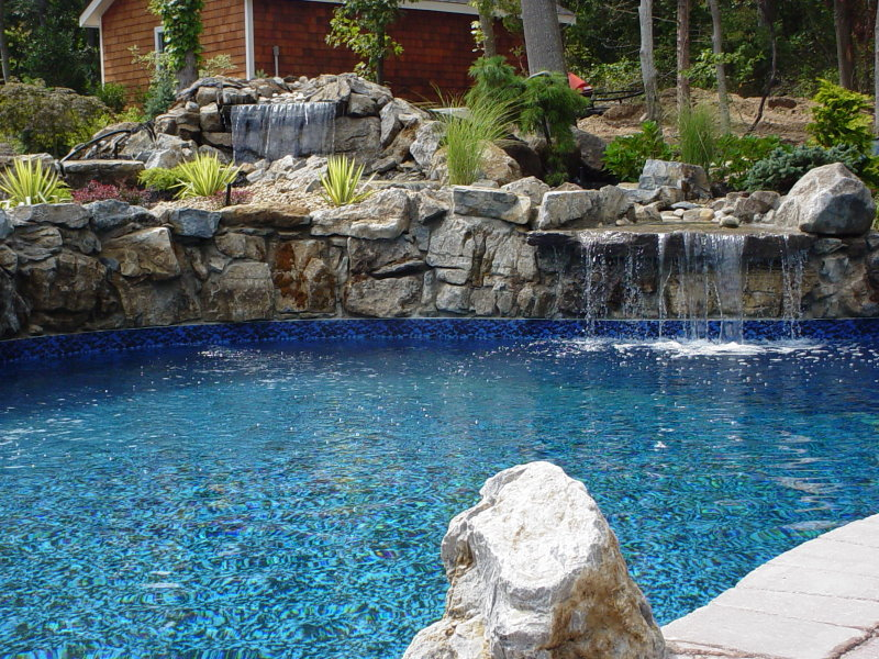 large moss rock waterfall in pool